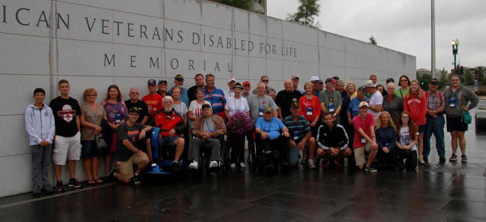 4 NHS students are pictured with several veterans they accompanied to Washington DC