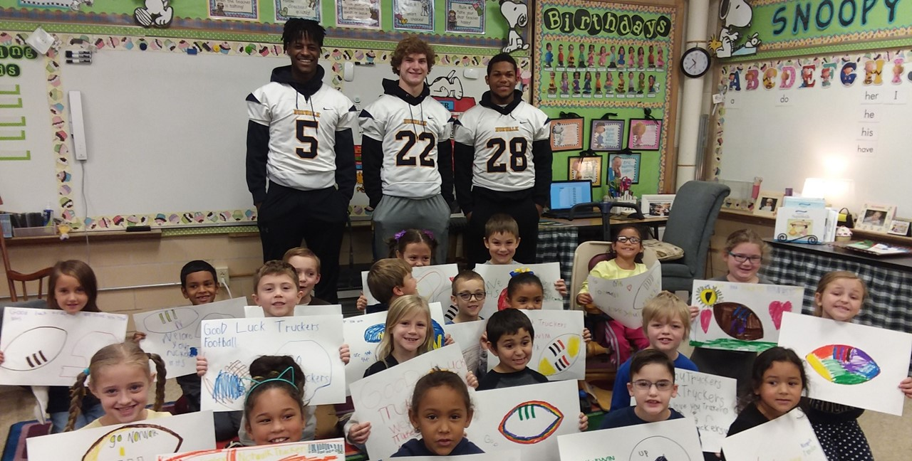 Football players visiting a Maplehurst classroom