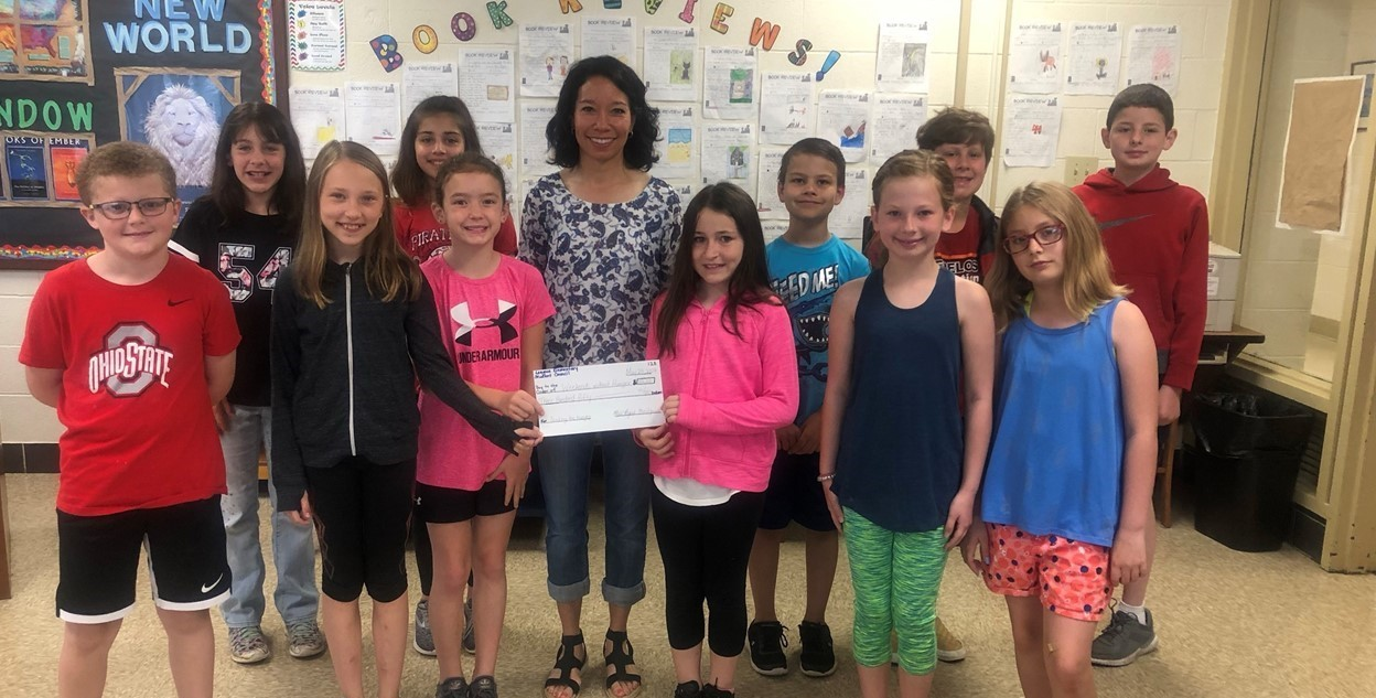 The League Elementary Student Council present a $350 check to the Weekends Without Hunger Organization. The group raised money by selling chocolate suckers throughout the school year which are made and donated by League teacher, Amy Krichbaum