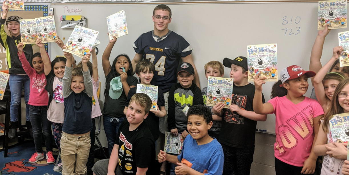 football players reading to elementary students
