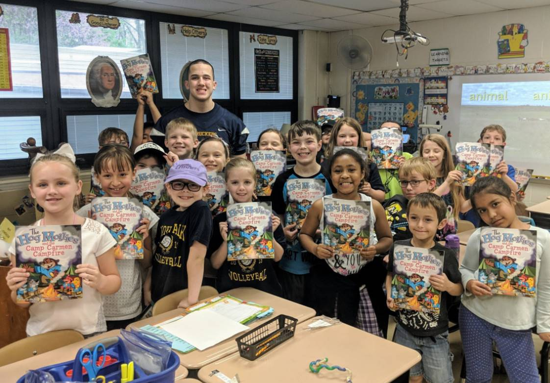 NHS Football player reads to elementary students